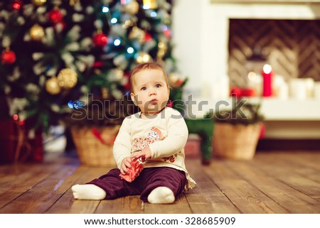 Chubby little cute baby girl 1 year old sitting on the floor in the New year, the Christmas lights and fireplace - stock photo