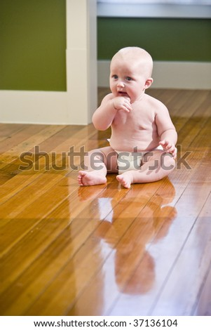 Chubby seven month old baby sitting on floor wearing diaper - stock photo