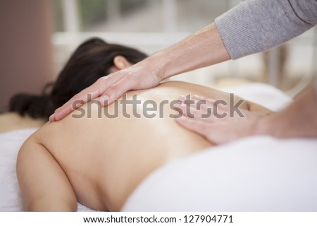 Chubby woman getting a massage at a health and beauty spa - stock photo