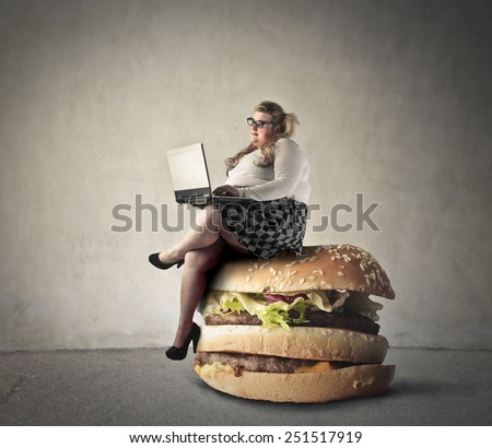 Chubby woman sitting on a giant hamburger  - stock photo