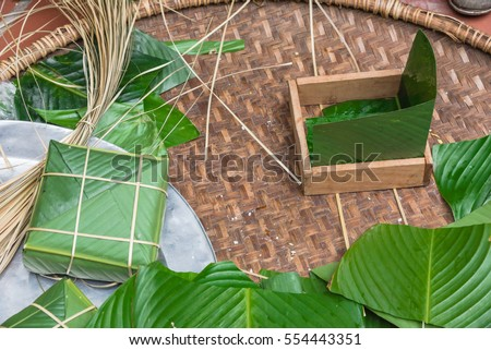 Chung Cake ingredients, tool preparation wrapping. Square shape wood mold with glutinous rice, split mung beans, chunks of pork shoulder, salt, pepper, ginger, bamboo, banana leaves, long node string.