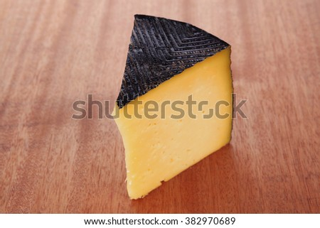 chunk of aged french gruyere or cheddar cheese in black shell on wooden table - stock photo