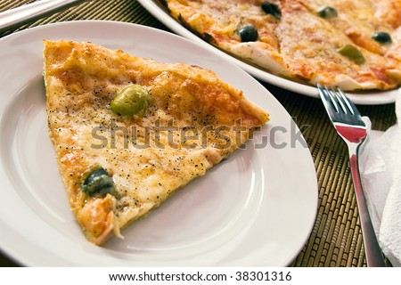 Chunk of delicious italian pizza with olives - stock photo