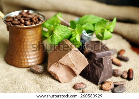 Chunks of chocolate with mint and coffee grains on burlap cloth background - stock photo