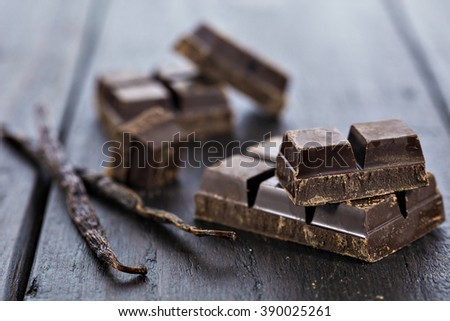 Chunks of dark chocolate bar and vanilla beans on wooden table background.