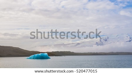 Chunks of glacial ice float in a calm lagoon named Jokulsarlon, or Glacier Lagoon in eastern Iceland. Black volcanic hills covered in snow bathed in sunlight and clouds in the background