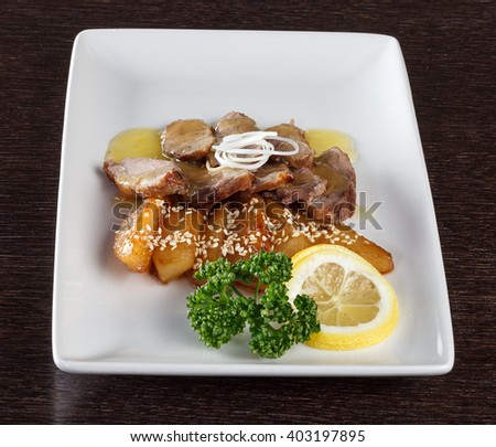 Chunks of tender veal meat with sauce, roast potatoes and a slice of lemon and parsley on white plate. European cuisine. Side view - stock photo