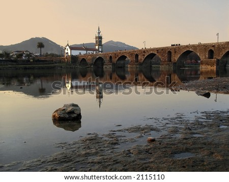 Church and ancient bridge over river Lima, Portugal. - stock photo