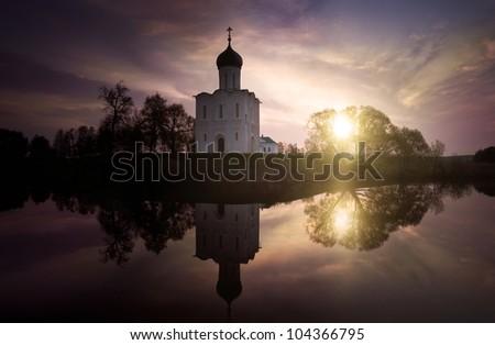 Church at sunset near lake - stock photo