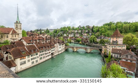 Church, bridge and houses with tiled rooftops, Bern, Switzerland. - stock photo