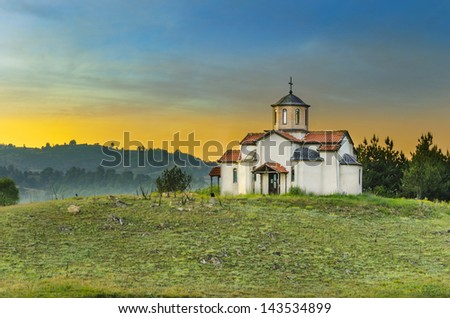 church building on the top of the heel at sunset with orange glow from sun - stock photo