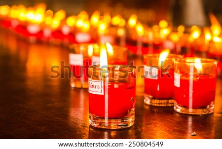 Church candles in red and yellow transparent chandeliers  - stock photo