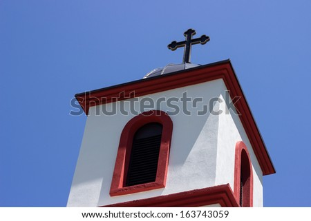 Church dome with cross on top. Sunny day with blue sky background.  - stock photo