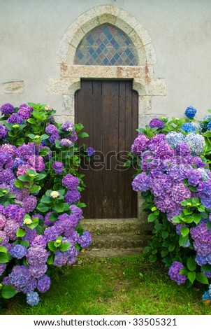 Church door surrounded by flowers in Brittany France