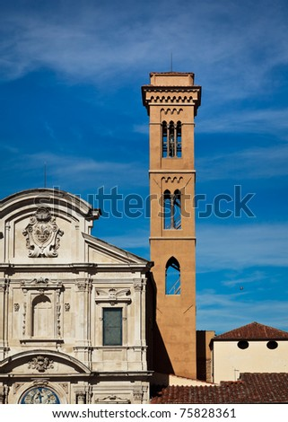 Church facade and bell-tower against slightly cloudy sky - stock photo