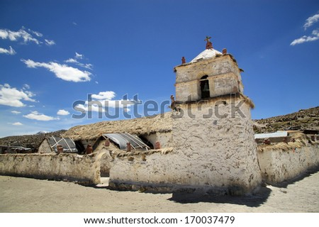 Church in Parinacota, Chile It was built in the 17th century in the form of a central nave with two side chapels. Walls are made of stone and clay and supported by exterior arches of unmortared stone. - stock photo