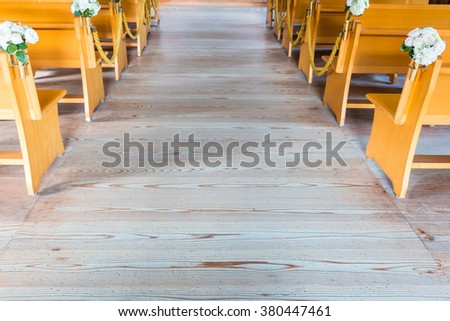 church interior with empty a row of wooden pews. - stock photo