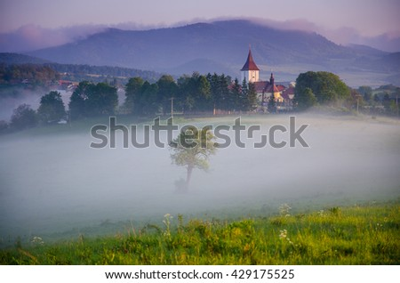 Church is hiding in the early morning fog in valley. A misty wallpaper with sunrise in the countryside. - stock photo
