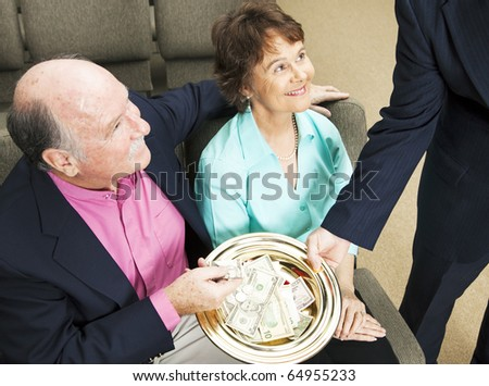 Church members placing money in the collection plate. - stock photo