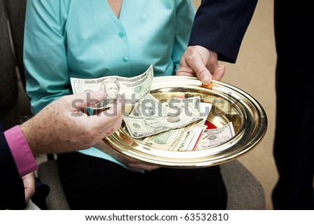 Church members putting money in the collection plate. - stock photo