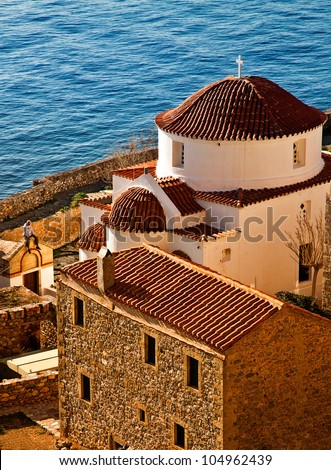 Church Of Castle Town Of Monemvasia With Man Sitting on Small Chapel. - stock photo