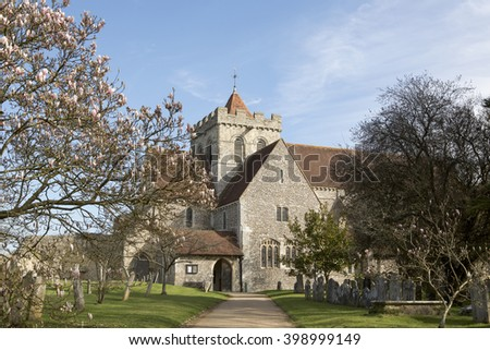 Church of St Mary and St Blaise on a spring morning in the village of Boxgrove in West Sussex. Path to main door framed by Magnolia trees. Typical English building in a rural setting.