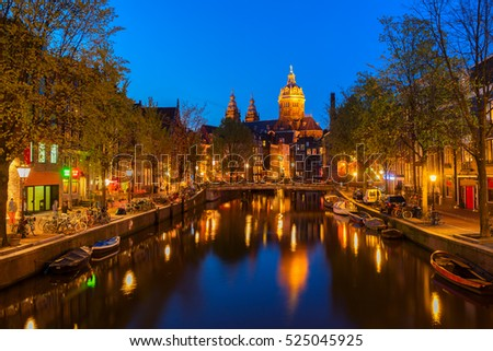 Church of St Nicholas and red lights quater over old town canal at night, Amsterdam, Holland