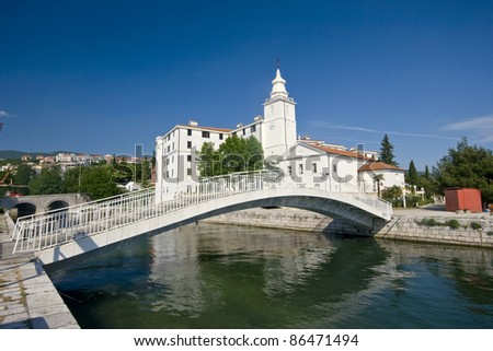 Church of the Resumption of the Blessed Virgin Mary and the bridge in Crikvenica - Stone bridge over the canal, old castle and church tower in Crikvenica - stock photo