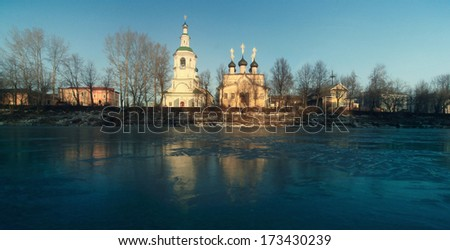 Church on the banks of the frozen river ice winter