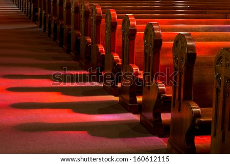 Church Pews in Reflected Stained Glass Lighting - stock photo