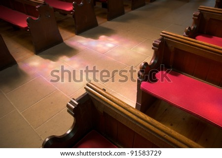 Church Seating With Stained Glass Light shining on the aisle - stock photo