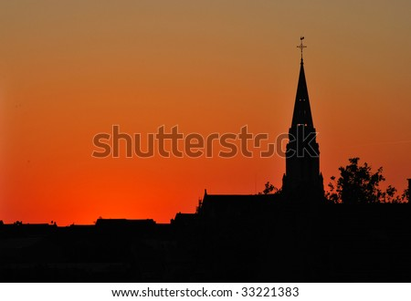 church silhouette on red and orange summer sunset - stock photo