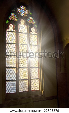 Church stained-glass window with sunlight shining through - stock photo
