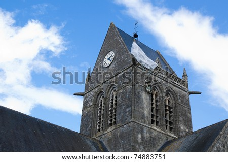 Church tower of Sainte-Mere-Eglise. On top landed a paratrooper on D Day. In memory of this soldier there is still hanging a dummy. Also film location for the film The Longest Day. D Day theme