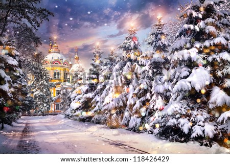 Church with illuminated Christmas trees in snowfall on Christmas eve in winter time - stock photo