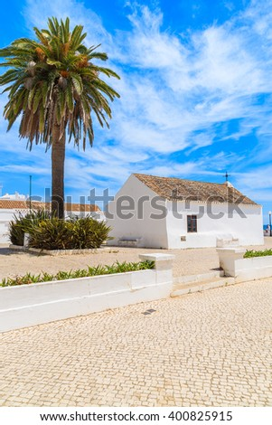 Church with palm tree on coastal promenade in seaside town of Armacao de Pera, Portugal