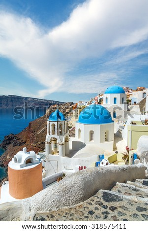 Churches of Oia village under puffy clouds, Santorini island, Greece