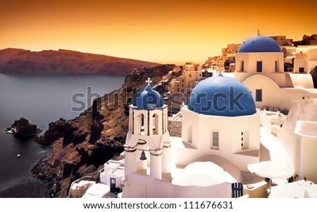 Churches on Santorini Cliffs with orange sky - stock photo