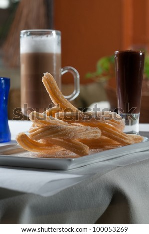 Churros with a dark chocolate sauce and a cup of coffee - stock photo