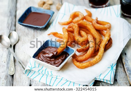 churros with chocolate sauce on a white wood background. toning. selective focus - stock photo