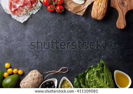 Ciabatta sandwich cooking with romaine salad, prosciutto and mozzarella cheese over stone background. Top view with copy space - stock photo