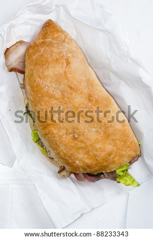 Ciabatta sandwich stuffed with meat and vegetables on white table - stock photo
