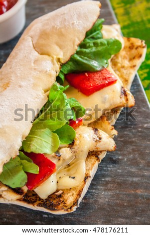 Ciabatta sandwich with chicken and cheese on wooden table. With fries and sauce