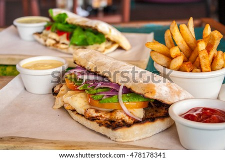 Ciabatta sandwich with chicken, arugula, fries, ketchup and cheese on wooden table