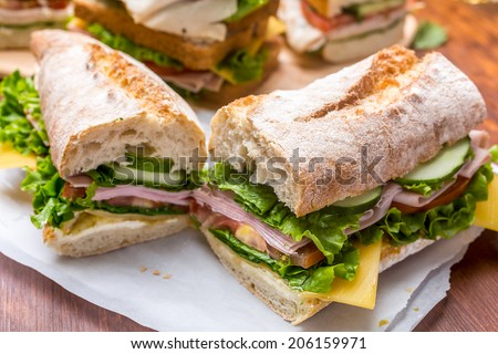 Ciabatta Sandwich with mustard, lettuce, slices of fresh tomatoes, ham, and cheese cut in half - stock photo