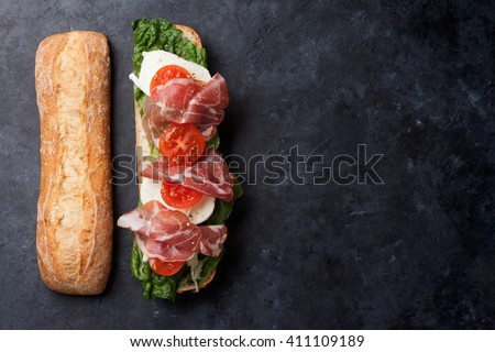 Ciabatta sandwich with romaine salad, prosciutto and mozzarella cheese over stone background. Top view with copy space - stock photo