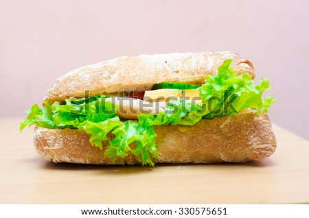 Ciabatta Sandwiche with lettuce, slices of fresh tomatoes, cucumber, ham, salami and cheese,horizontal photo