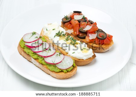 ciabatta with tomatoes, goat cheese, pate with green peas and radish on white plate, horizontal - stock photo
