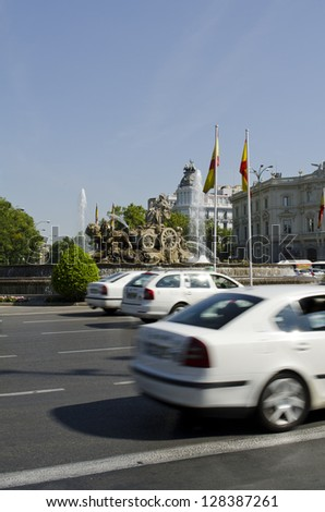 Cibeles Fountain in Plaza de la Cibeles, downtown of Madrid. Blurred cars in foreground. - stock photo