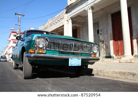 CIENFUEGOS, CUBA - FEBRUARY 3: Classic Soviet Volga car parked in the street on February 3, 2011 in Cienfuegos, Cuba. The multitude of oldtimer cars in Cuba is its major tourism attraction. - stock photo